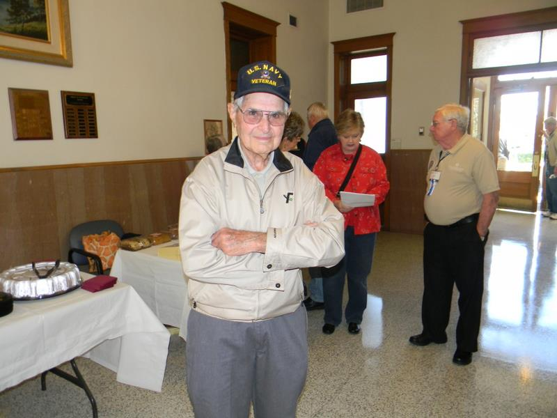 Man in khkai jacket and crossed arms, wearing Navy Veteran hat, smiles for camera